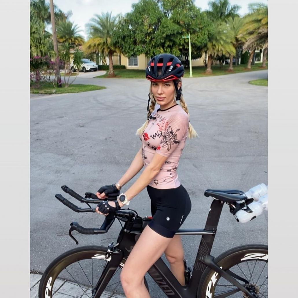 Nadezhda Pavlova standing by bike, looking to side in Girls Rule pink kit